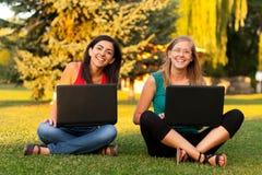 Filles riantes à l'extérieur avec l'ordinateur portatif Photos stock