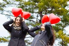 Filles riantes jouant et tenant des ballons Photographie stock libre de droits