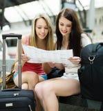 Filles s'asseyant à la gare avec la carte Photo libre de droits