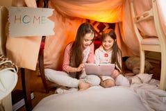 Filles s'asseyant dans la maison faite de couvertures et à l'aide du comprimé numérique Photos libres de droits