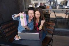 Filles s'asseyant devant l'ordinateur portable et le sourire Photos libres de droits