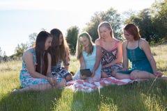 Filles s'asseyant ensemble dans le domaine herbeux avec la lumière du soleil au-dessus Image libre de droits