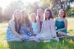 Filles s'asseyant ensemble dans le domaine herbeux avec la lumière du soleil au-dessus Image stock
