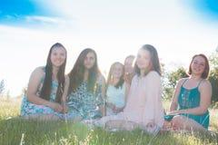Filles s'asseyant ensemble dans le domaine herbeux avec la lumière du soleil au-dessus Photos stock