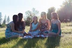 Filles s'asseyant ensemble dans le domaine herbeux avec la lumière du soleil au-dessus Photo libre de droits