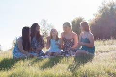 Filles s'asseyant ensemble dans le domaine herbeux avec la lumière du soleil au-dessus Images libres de droits
