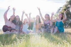 Filles s'asseyant ensemble dans le domaine herbeux chantant et jouant la musique Images libres de droits
