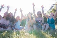 Filles s'asseyant ensemble dans le domaine herbeux chantant et jouant la musique Photos stock