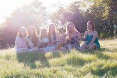 Filles s'asseyant ensemble dans le domaine herbeux chantant et jouant la musique Photographie stock