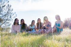 Filles s'asseyant ensemble dans le domaine herbeux chantant et jouant la musique Photographie stock libre de droits