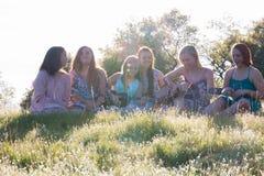 Filles s'asseyant ensemble dans le domaine herbeux chantant et jouant la musique Photos libres de droits