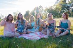 Filles s'asseyant ensemble dans le domaine herbeux chantant et jouant la musique Image stock