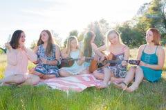 Filles s'asseyant ensemble dans le domaine herbeux chantant et jouant la musique Image libre de droits