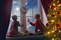 Filles s'asseyant par la fenêtre Photographie stock libre de droits