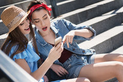 Filles s'asseyant sur des escaliers avec le téléphone Image libre de droits