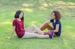 Filles s'asseyant sur l'herbe verte après exercice Photographie stock libre de droits