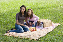 Filles s'asseyant sur la couverture de pique-nique sur l'herbe en stationnement image stock
