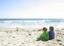 Filles s'asseyant sur la plage Photo stock