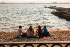 Filles s'asseyant sur la plage au coucher du soleil Photographie stock libre de droits