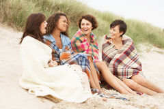 Filles s'asseyant sur la plage ensemble Photos stock