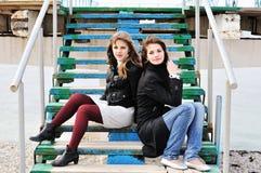 Filles s'asseyant sur les escaliers Image libre de droits