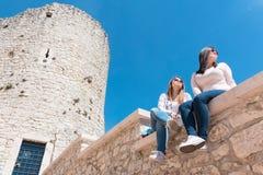 Filles s'asseyant sur un mur Photo libre de droits