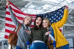 Filles satisfaisantes soulevant le drapeau au-dessus de leurs têtes Photos stock