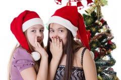 Filles se partageant secrets le réveillon de Noël Photographie stock