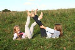 Filles se situant dans l'herbe Photographie stock libre de droits