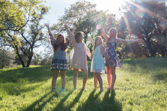 Filles se tenant avec des bras augmentés et des frais généraux de lumière du soleil Photographie stock