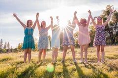 Filles se tenant avec des bras augmentés et des frais généraux de lumière du soleil Image stock