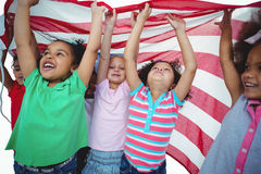 Filles se tenant avec le drapeau américain aérien Images libres de droits