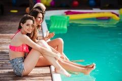 Filles sexy assez jeunes ayant l'amusement à la piscine Photographie stock