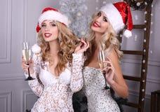 Filles sexy dans le chapeau de Santa et des robes luxueuses, champagne potable Photographie stock libre de droits