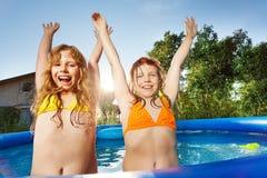 Filles soulevant leurs mains se levant dans la piscine Photo stock