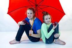 Filles sous le parapluie rouge Photo stock