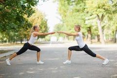 Filles sportives, attirantes, convenables établissant ensemble sur un fond de parc Concept de gymnastique Photos stock