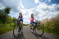 Filles sur des bicyclettes d'une équitation de voyage Images libres de droits
