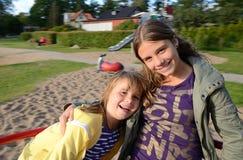 Filles sur le carrousel de cour de jeu Photo libre de droits