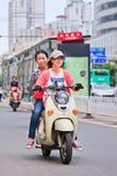 Filles sur un e-vélo au centre de la ville, Kunming, Chine Photos stock