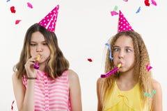 Filles sur un fond blanc, dans des chapeaux de fête, soufflant dans les tuyaux, confettis colorés Image stock