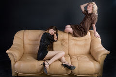 Filles sur un sofa brun Photo stock