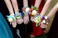 Filles tenant des bras avec des fleurs de corsage pour le bal d'étudiants Images libres de droits
