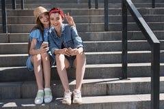 Filles tenant des smartphones tout en se reposant sur les escaliers Photo libre de droits