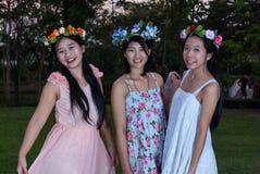 Filles thaïlandaises asiatiques avec la couronne de fleur en parc Image stock