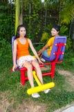 Filles thaïlandaises asiatiques avec la machine d'exercice en parc public Photographie stock