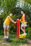 Filles thaïlandaises asiatiques avec la machine d'exercice en parc public Photo libre de droits