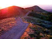 Filles trimardant sur des montagnes au coucher du soleil Image stock