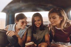 Filles voyageant en une voiture et regardant le téléphone Image libre de droits