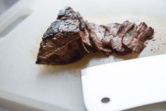 A fillet of beef steak. Close-up look of a fillet of partially burn beef steak on cutting board with half of the piece cut with the cleaver on the side Royalty Free Stock Photos
